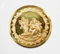 A Tanishq gold coin, depicting two Hindu figures, stamped 995 fine gold, 10g, in presentation sleeve