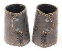 A pair of American leather arm cuffs, each with straps and two button design, 17cm high.