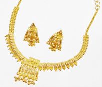 An Indian dress necklace and earring set, the necklace with central shaped panel with filigree