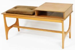 A 1970's/80's teak telephone table, with brown upholstered rectangular seat, and single shelf on