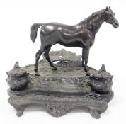 A bronze desk stand mounted as a standing horse, on a rustic stand incorporating two ink recesses