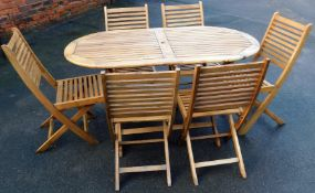 A teak garden table and chair set, the oval table with six folding chairs and an additional metal