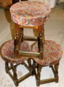 *Three framed pub stools, each with floral upholstered tops on wooden base,with brass bars, 52cm