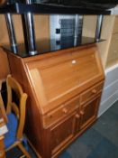 A pine bureau, 114cm high, 93cm wide, 47cm deep., together with a glass television stand. (2)