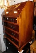 A yew wood bureau with fitted interior, above four drawers, 100cm high, 74cm wide, 47cm deep.