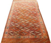 A Tekke Turkoman type carpet, with a lozenge design in blue and red, on a brown ground with one wide