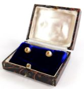 A pair of cultured pearl earrings, each with single pearl and gold six point flower end, on screw on