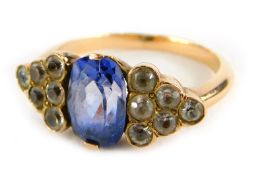An Art Deco style ring, with oval cut pale blue sapphire, flanked by triangle staggered design set