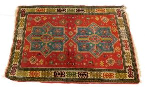 A Kazak` type rug, with two turquoise and red geometric medallions, on a red ground with one wide