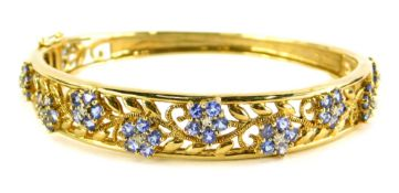 A hinged bangle, the top floral engraved design set with purple coloured stones and central CZ