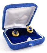 A pair of sapphire and diamond earrings, each with central cabochon cut sapphire in four claw