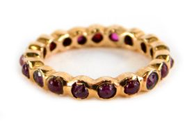 A garnet eternity ring, set with various cabochon cut stones, in a rose gold coloured setting,