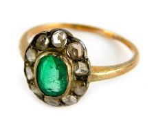 An emerald and diamond dress ring, in floral cluster with central oval cut emerald, surrounded by