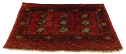 A Turkoman type rug, with a design of nine medallions on a red ground with multiple borders, 175cm x