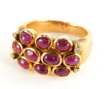 A ruby and diamond dress ring, with three rows of cabochon cut rubies and four tiny diamonds, on a