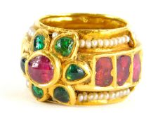 An Indian dress ring, set with various cabochon cut rubies, emeralds and seed pearls, the centre
