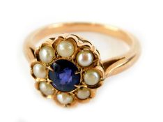 A sapphire and seed pearl daisy ring, the central oval cut sapphire surrounded by seed pearls, in