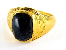 A garnet set signet ring, the setting of hammered design with scroll design shoulders and etched