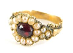 A Victorian memorial ring, set with cabochon garnet stone, surrounded by seed pearls,