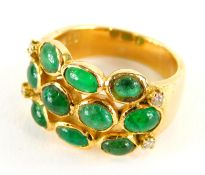 An emerald and diamond set dress ring, with three row design of cabachon emeralds, with four tiny