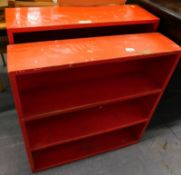 Two red painted open bookcases.