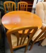 A circular teak extending dining table and four chairs.
