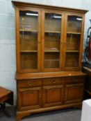 A Stag minstrel type mahogany display cabinet, with three glazed doors and three drawers and