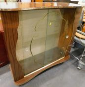 A 1960s melamine display cabinet, with glass sliding doors and shelves, 103cm wide.