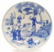 A Chinese blue and white plate, profusely decorated with figures before trees, with a double line