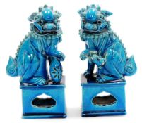 A pair of Chinese turquoise glazed pottery dogs of fo, each on shaped partially pierced bases,