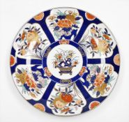 A Japanese Imari charger with basket of flowers, surrounded by panels of floral bouquets on a blue
