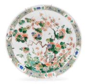 A Chinese Kangxi porcelain dish, profusely decorated with flowering shrubs, predominantly in orange,