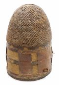 A 20thC African hide and woven measuring guard, with leather insert and entwined woven top, 28cm