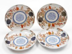 A set of four Japanese Imari porcelain plates, decorated with figures among bamboo and prunus,
