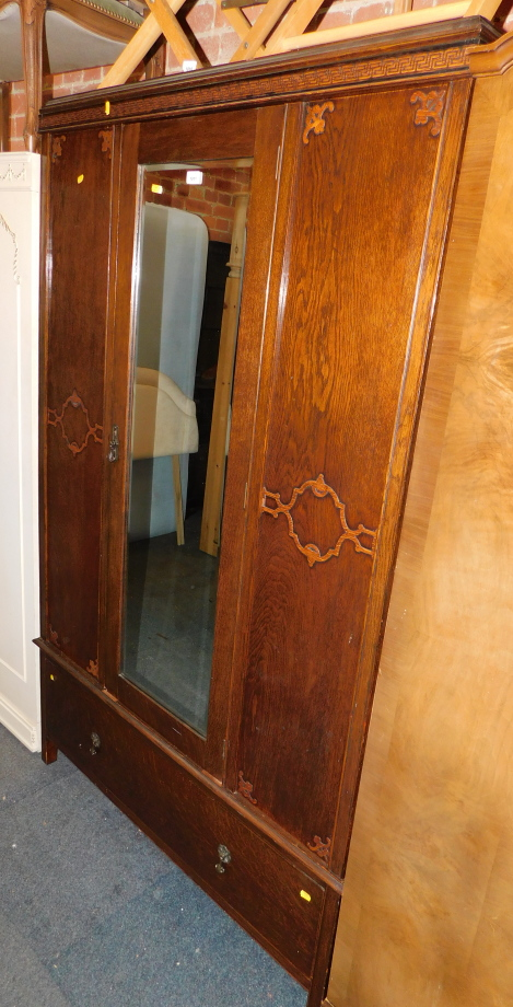An early 20thC oak and oak veneered wardrobe, with central mirrored door above single drawer,