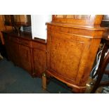 A reproduction burr walnut break front sideboard, with four drawers above four cupboard doors,