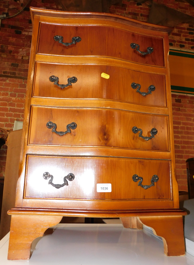 A reproduction yew wood serpentine fronted chest, of four drawers, 70cm high, 48cm wide, 36cm deep.