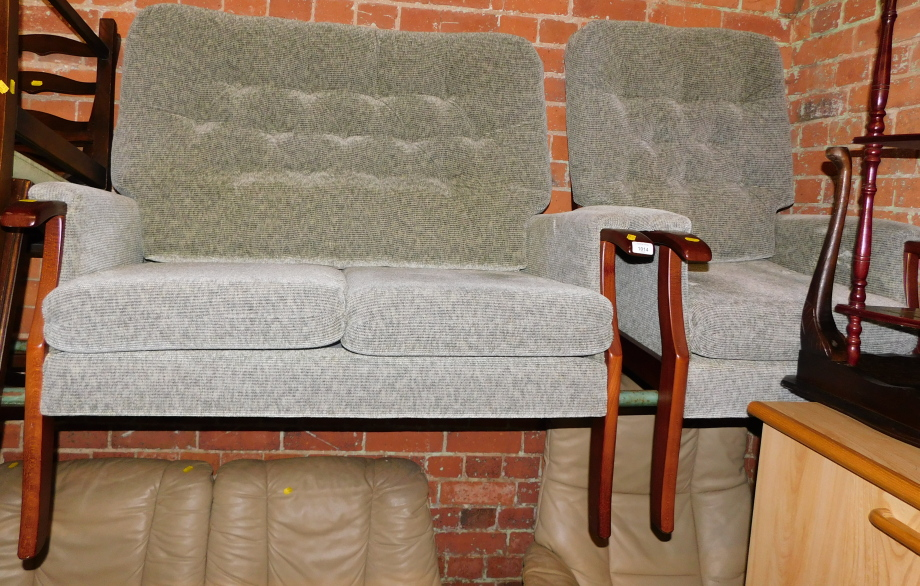 A two seater wooden framed sofa, upholstered in green fabric, together with a matching armchair. (