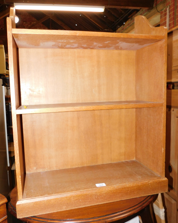 A blonde oak floor standing bookcase, of two shelves, 81cm high, 64cm wide, 23cm deep.