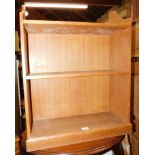 A blonde oak floor standing bookcase, of two shelves, 81cm high, 64cm wide, 23cm deep.