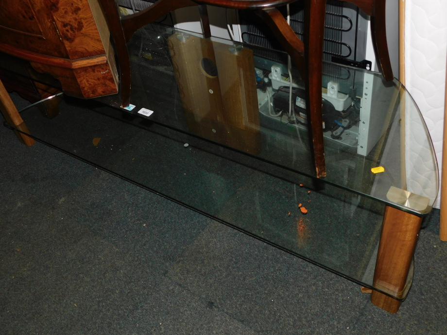 A glass television stand, with lower shelf, and oak effect supports, 41cm high, 151cm wide, 40cm