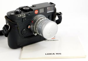 A black Leica M6 camera, with a Leitz 5cm f2 Summicron lens, number 1581384, and a half leather case