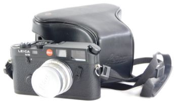 A black Leica M6 camera, with a Leitz 35mm f wide angle Summicron lens, number 1745070, in a leather