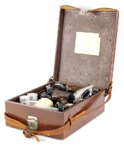 A brown leather Leitz Leica case, containing mixed Leica accessories.