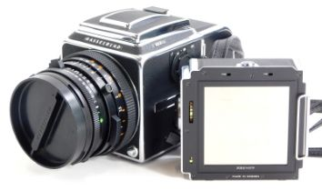 A Hasselblad 503CX camera, with Zeiss Planar f2.8 80mm lens, two A12 film backs and lens hood, in a