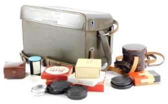A brown leather Leica holdall case, containing mixed Leica accessories.