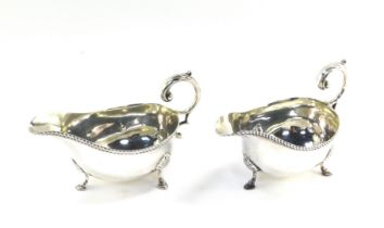 A pair of Edward VII silver sauce boats, with leaf scroll handles, gadrooned rims and raised on thre