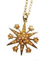 An Edwardian pendant and chain, the star pendant set with various seed pearls, in a yellow metal bac