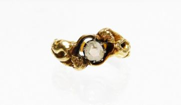 A modern dress ring, depicting two mermaids holding a central imitation diamond, on a yellow metal b