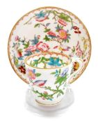 A Minton cup and saucer, profusely decorated with flowers birds and vines, marked English porcelain